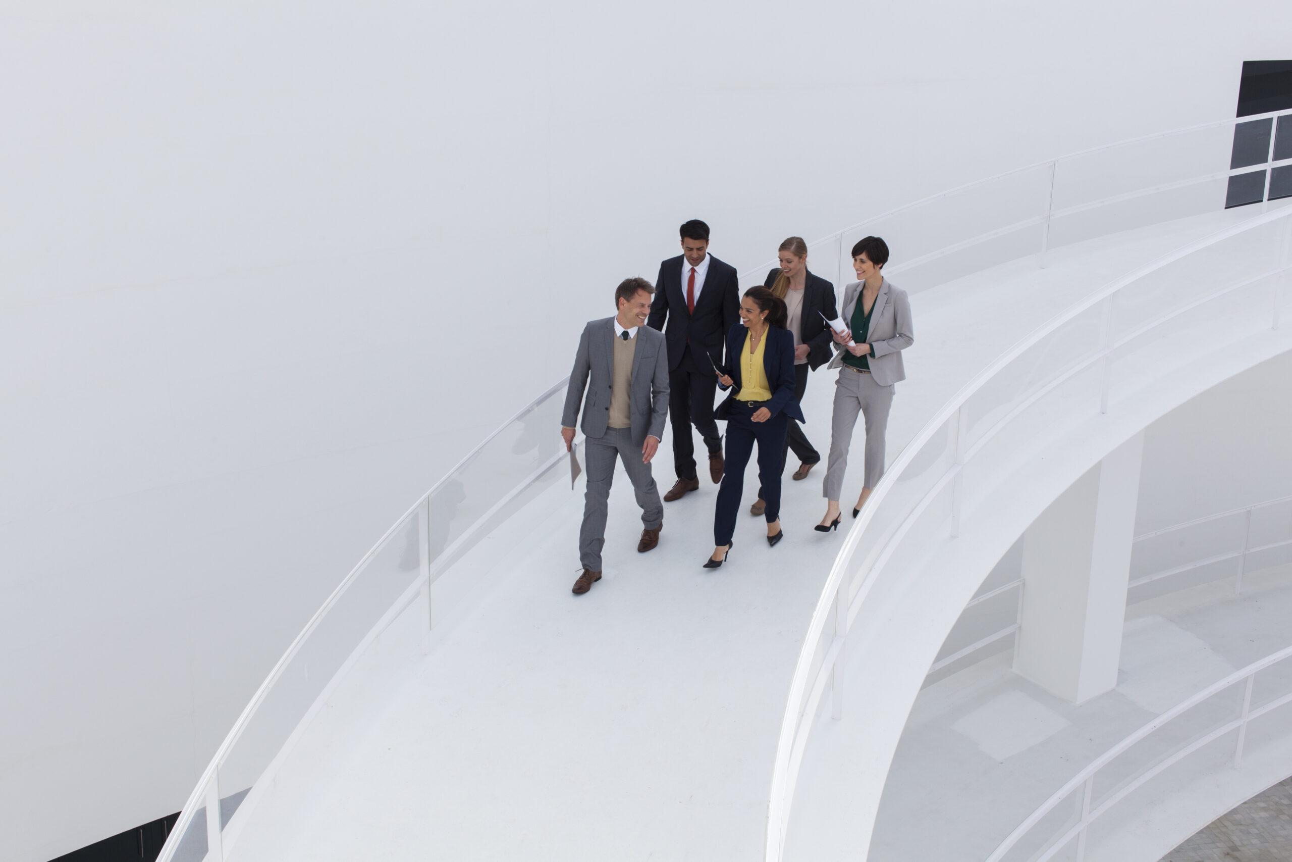 Corporate business people walking on modern ramp